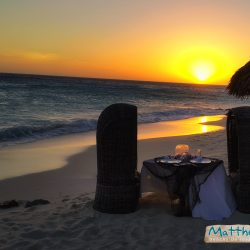 Two chairs and a table set for two on the beach with the sea and sunset in the back