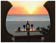 Table set for two overlooking the beach, sea and a gorgeous sunset