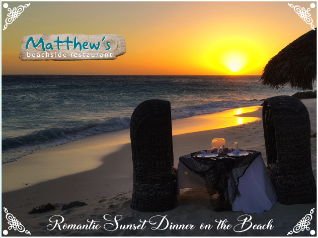 Two chairs and a table, set for two, on the beach near the sea with a gorgeous sunset in the background