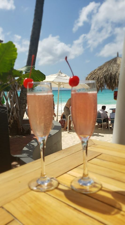 Two drinks on a table with a backdrop of the beach and ocean